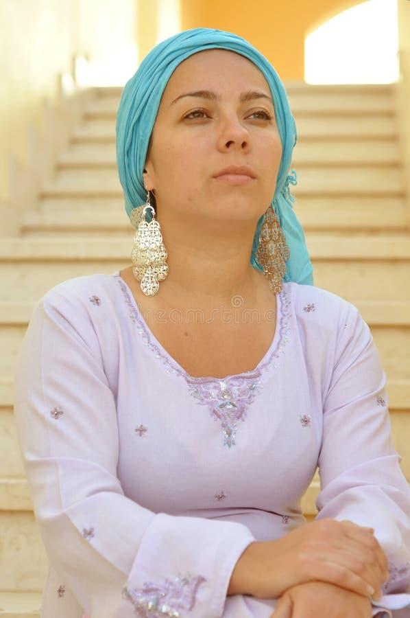 Muchacha con una bufanda en su cabeza que se sienta en los pasos y que mira en la distancia imagenes de archivo