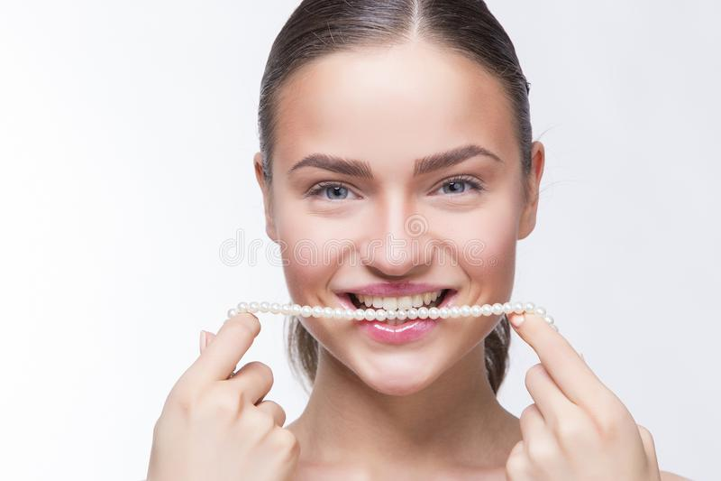 Muchacha con una cadena de perlas en su boca foto de archivo