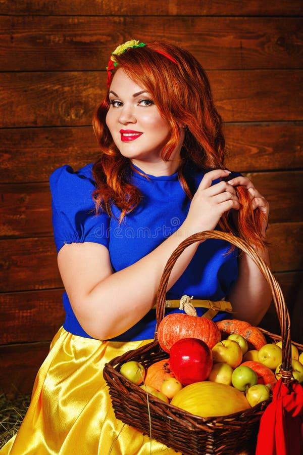 Muchacha con una cesta con una cosecha de verduras y de la fruta foto de archivo libre de regalías