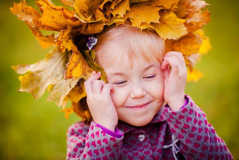 Muchacha con una guirnalda de hojas de arce en la cabeza fotos de archivo