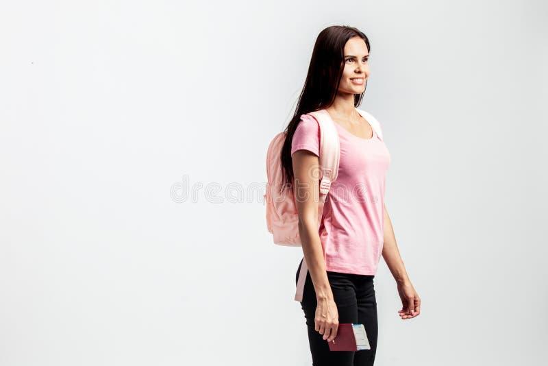 Muchacha con una mochila en sus hombros vestido en la camiseta rosada imagenes de archivo