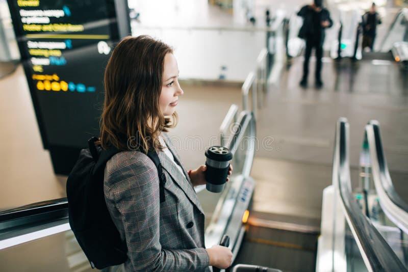 Muchacha con una mochila que va abajo de la escalera móvil en el airpot fotografía de archivo