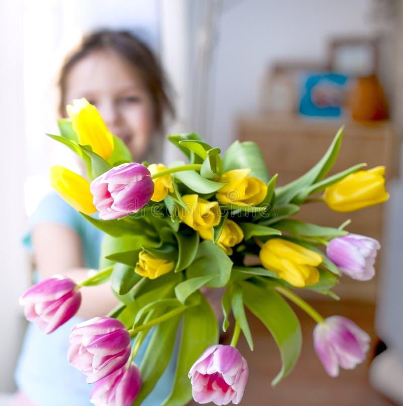 Muchacha con una nota de las flores de la primavera EN una casa acogedora en la sala de estar por la ventana Tulipanes de diverso fotos de archivo