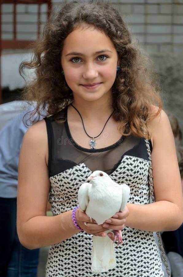 Muchacha con una paloma en sus manos fotografía de archivo