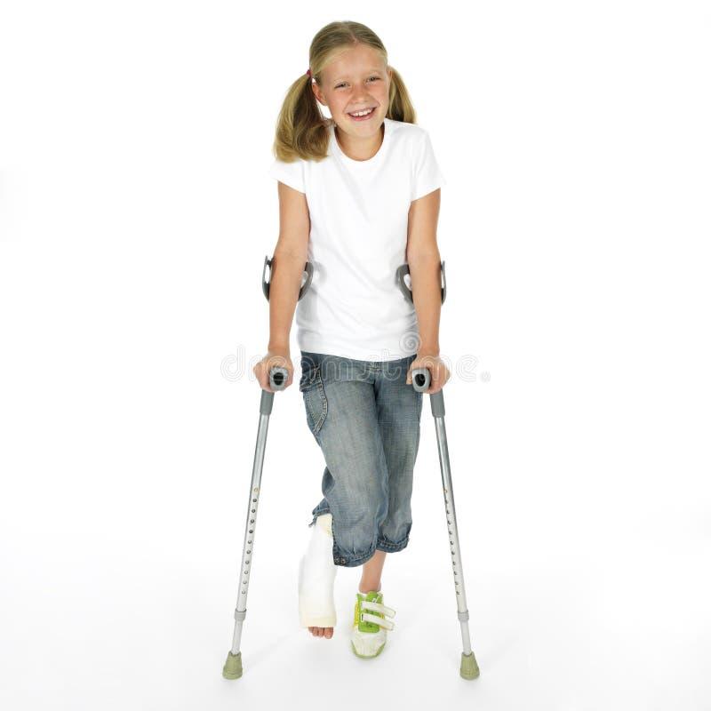 Muchacha con una pierna quebrada que recorre en las muletas imagenes de archivo