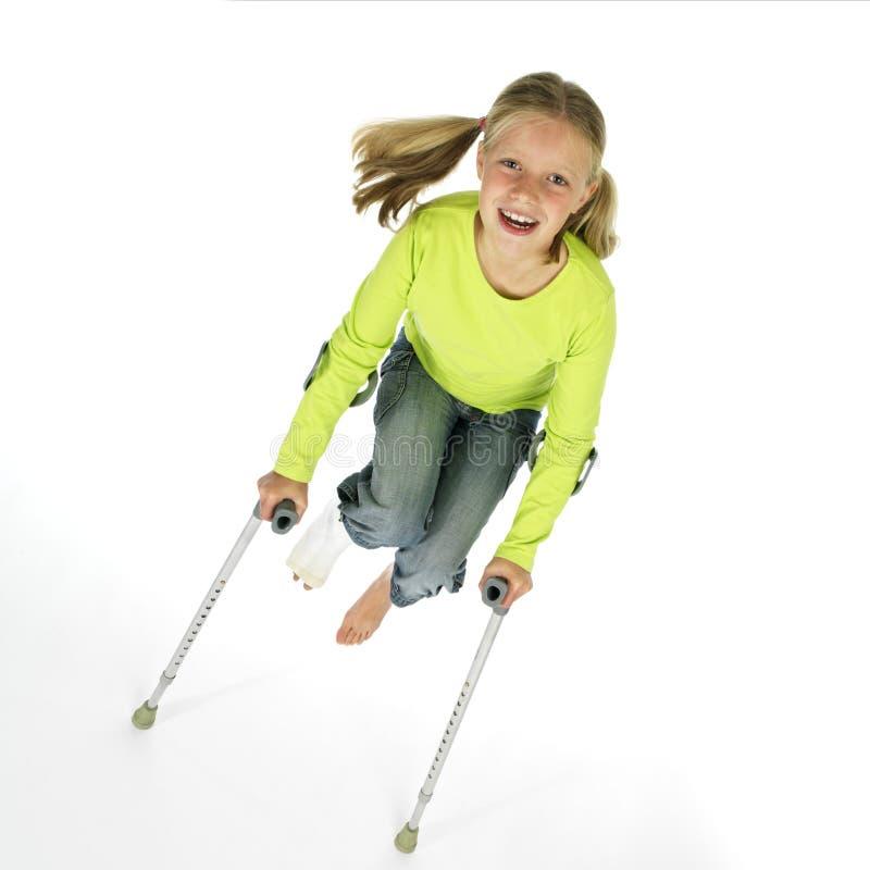 Muchacha con una pierna quebrada que salta en las muletas foto de archivo