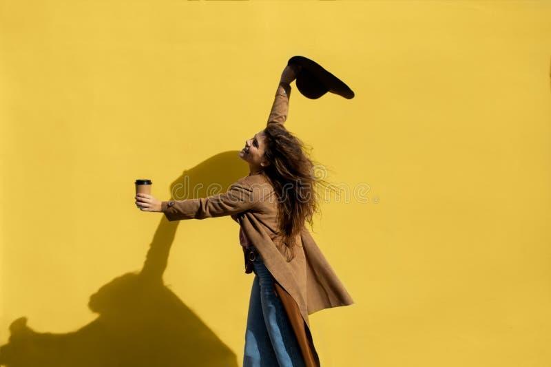 Muchacha con una taza de café en un día soleado cerca de la pared amarilla fotos de archivo libres de regalías