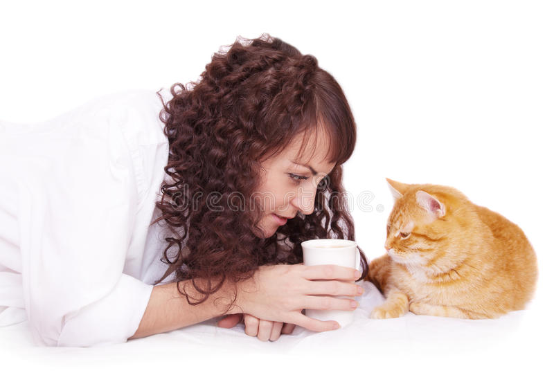 Muchacha con una taza de café y de su gato en cama imagenes de archivo