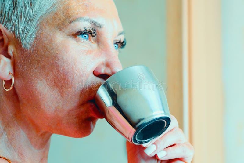 Muchacha con una taza de caf? Caf? de la ma?ana Mujer que sostiene una taza de café sólo, sentándose en la ventana La chica joven foto de archivo libre de regalías