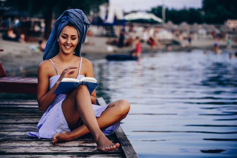 Muchacha con una toalla en su cabeza que lee un libro mientras que se sienta en la playa imagenes de archivo
