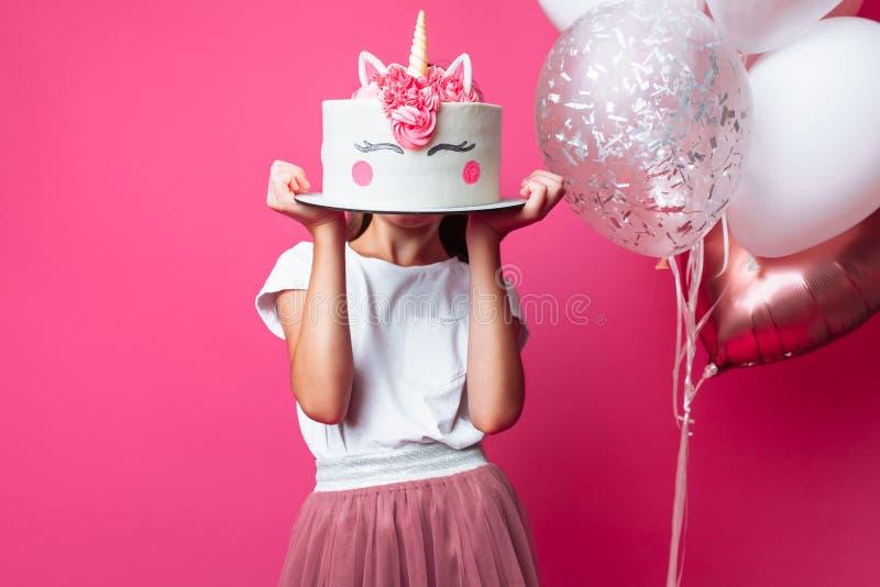 Muchacha con una torta para un cumpleaños, en el estudio en un fondo rosado, humor festivo, cierre - para arriba, torta del diseñ fotografía de archivo libre de regalías