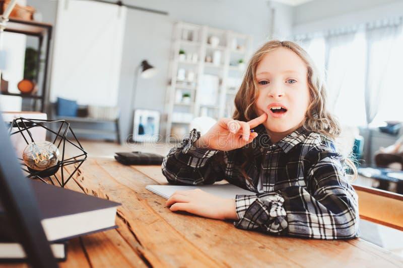 muchacha concentrada del niño que hace la preparación Niño pensativo de la escuela que piensa y que busca una respuesta fotografía de archivo
