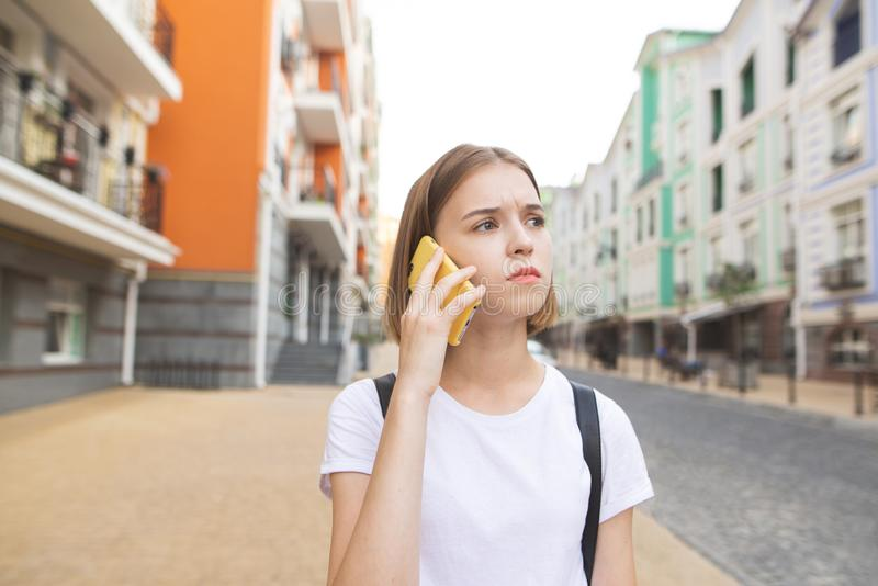 Muchacha concentrada en una camiseta blanca, hablando en el smartphone en la calle y mirando lejos fotografía de archivo