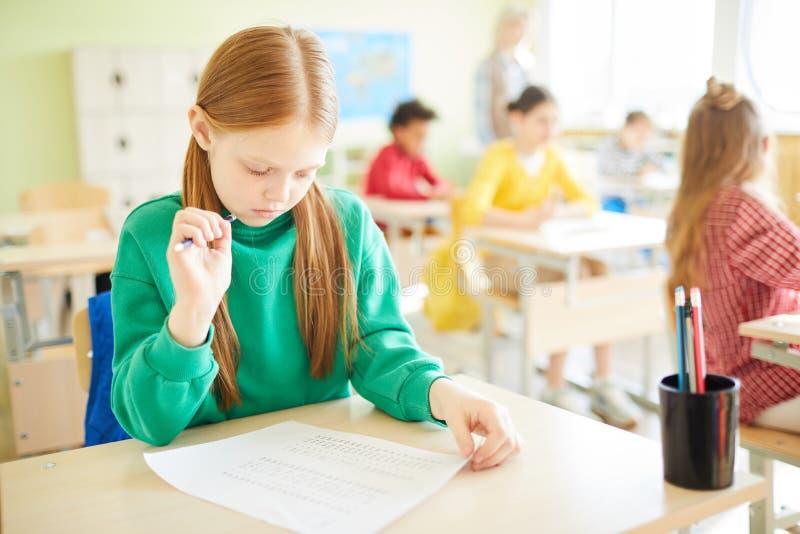 Muchacha concentrada que comprueba la prueba antes de dar vuelta en él imagenes de archivo