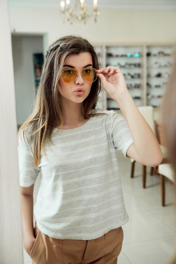 Muchacha confiada atractiva que intenta en gafas elegantes mientras que al hacer compras en tienda del óptico La mujer fue a comp fotos de archivo