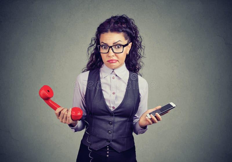 Muchacha confusa con los teléfonos viejos y nuevos imagen de archivo
