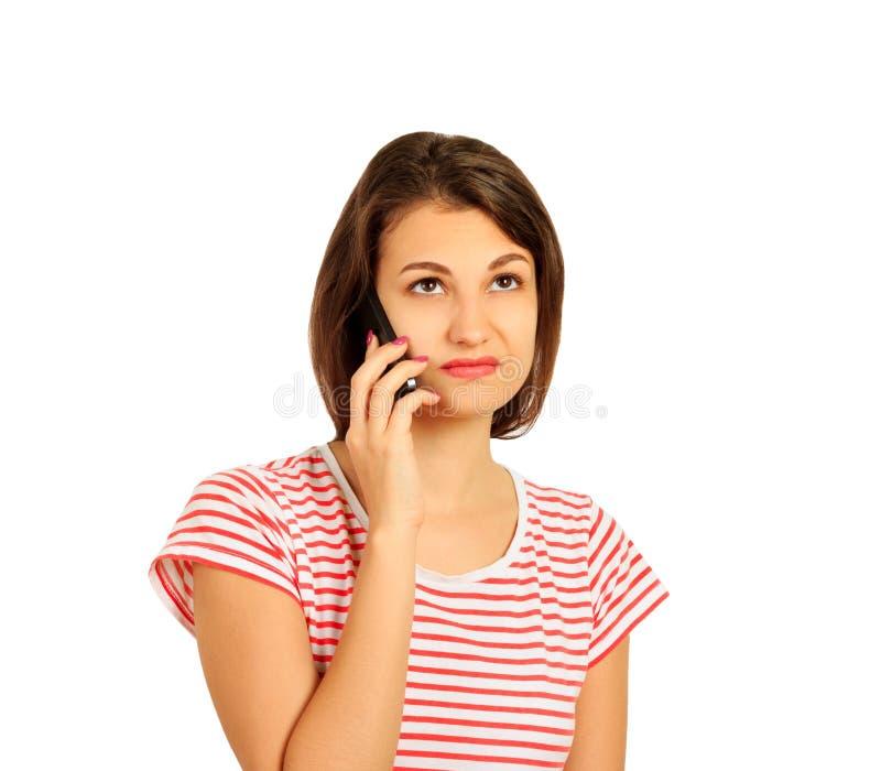 Muchacha contrariedad que habla en el teléfono móvil mire con perplejidad muchacha emocional aislada en el fondo blanco fotos de archivo libres de regalías