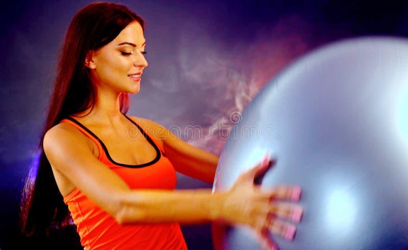 Muchacha contratada a actividad del deporte del fitball foto de archivo