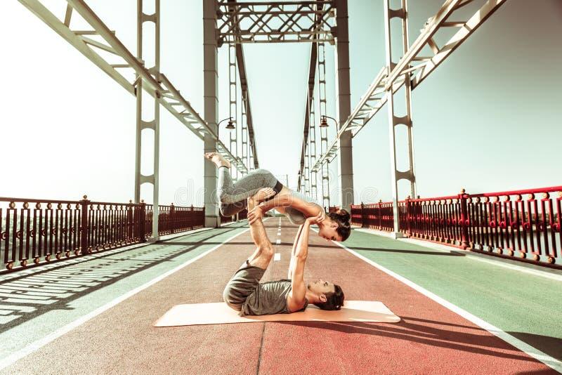 Muchacha contratada a yoga acrobática con su socio foto de archivo