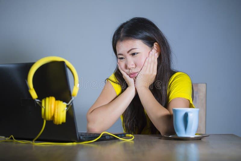 Muchacha coreana asiática bonita y aburrida joven del estudiante que trabaja con el ordenador portátil que mira cara que se sosti fotos de archivo libres de regalías