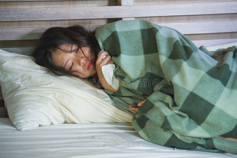 Muchacha coreana asiática dulce en los pijamas cubiertos con frío enfermo y la gripe sufridores de la manta que toman temperatura imagen de archivo
