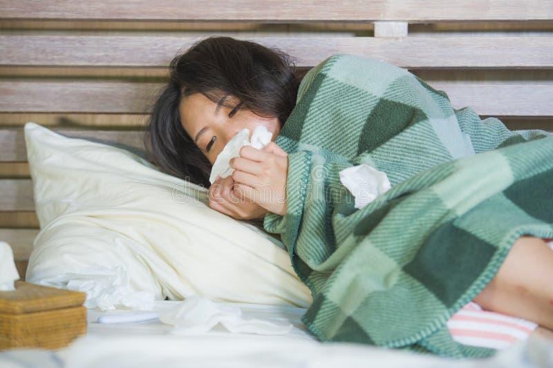 Muchacha coreana asiática dulce en los pijamas cubiertos con frío enfermo y la gripe sufridores de la manta que toman temperatura fotografía de archivo libre de regalías