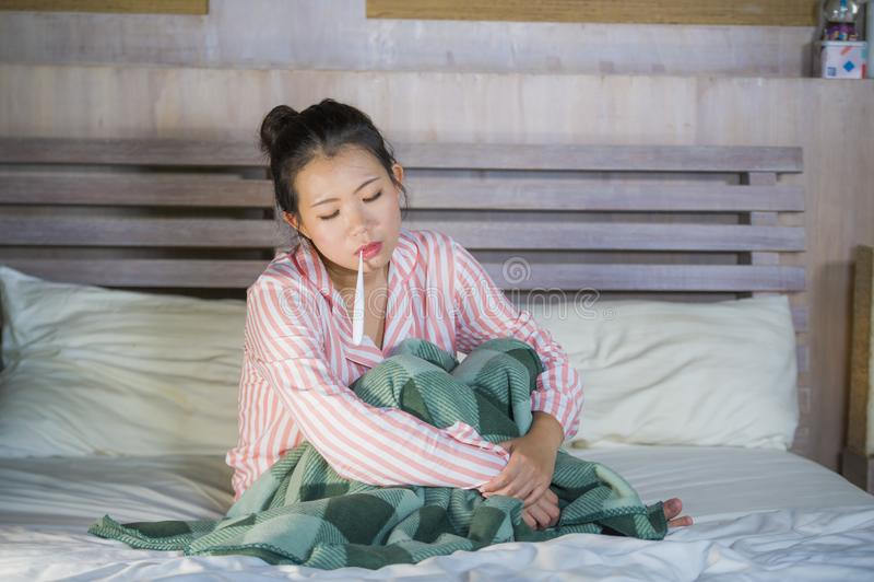 Muchacha coreana asiática dulce en los pijamas cubiertos con frío enfermo y la gripe sufridores de la manta que toman temperatura foto de archivo libre de regalías