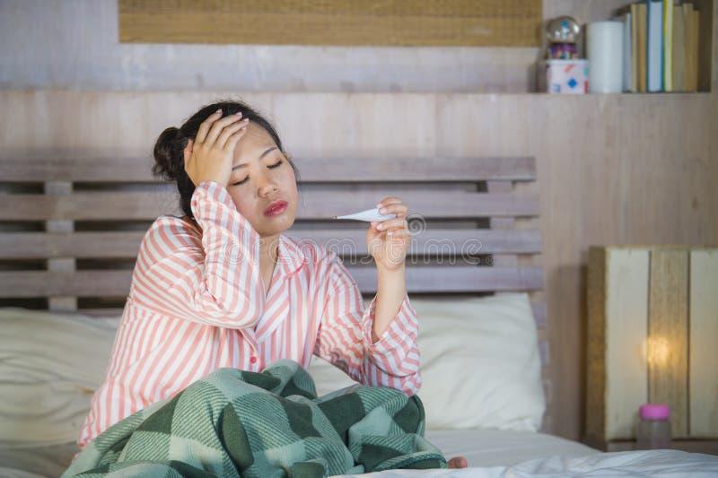 Muchacha coreana asiática dulce en los pijamas cubiertos con frío enfermo y la gripe sufridores de la manta que toman temperatura fotos de archivo libres de regalías