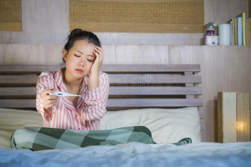 Muchacha coreana asiática dulce en los pijamas cubiertos con frío enfermo y la gripe sufridores de la manta que toman temperatura imagenes de archivo
