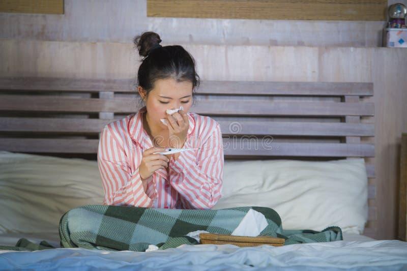 Muchacha coreana asiática dulce en los pijamas cubiertos con frío enfermo y la gripe sufridores de la manta que toman temperatura fotografía de archivo