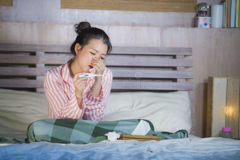 Muchacha coreana asiática dulce en los pijamas cubiertos con frío enfermo y la gripe sufridores de la manta que toman temperatura fotos de archivo