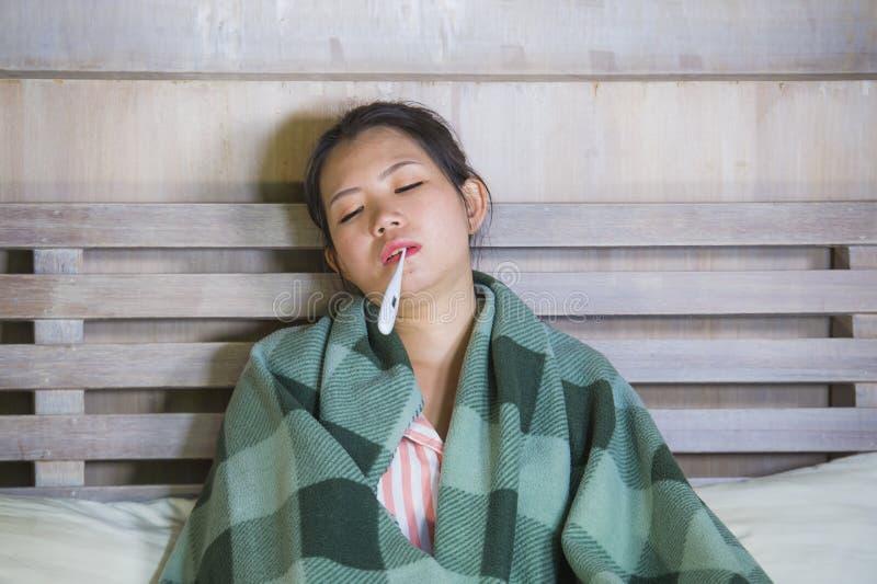 Muchacha coreana asiática dulce en los pijamas cubiertos con frío enfermo y la gripe sufridores de la manta que toman temperatura foto de archivo