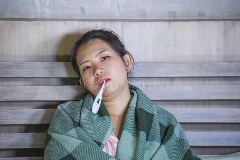 Muchacha coreana asiática dulce en los pijamas cubiertos con frío enfermo y la gripe sufridores de la manta que toman temperatura imagen de archivo libre de regalías