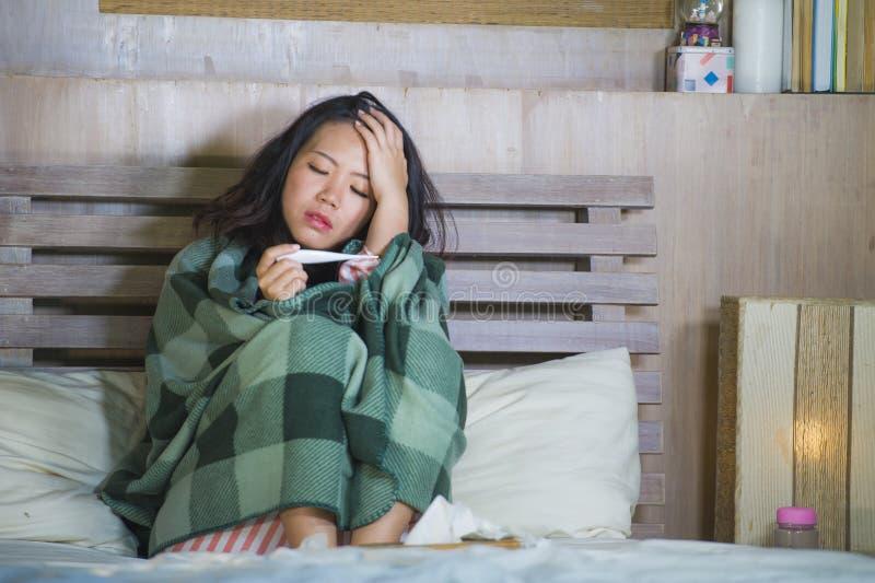 Muchacha coreana asiática dulce en los pijamas cubiertos con frío enfermo y la gripe sufridores de la manta que toman temperatura imágenes de archivo libres de regalías