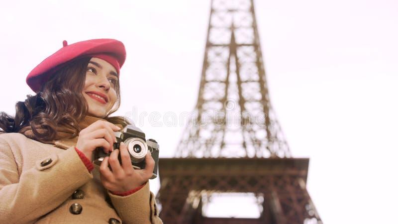 Muchacha creativa que sostiene la cámara en las manos, disfrutando de la afición de la fotografía en París fotografía de archivo libre de regalías