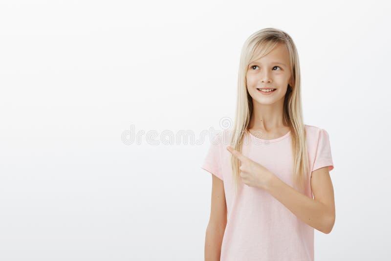 Muchacha creativa soñadora que ve algo el sorprender Retrato del niño femenino adorable positivo con el pelo rubio, mirando y imagenes de archivo
