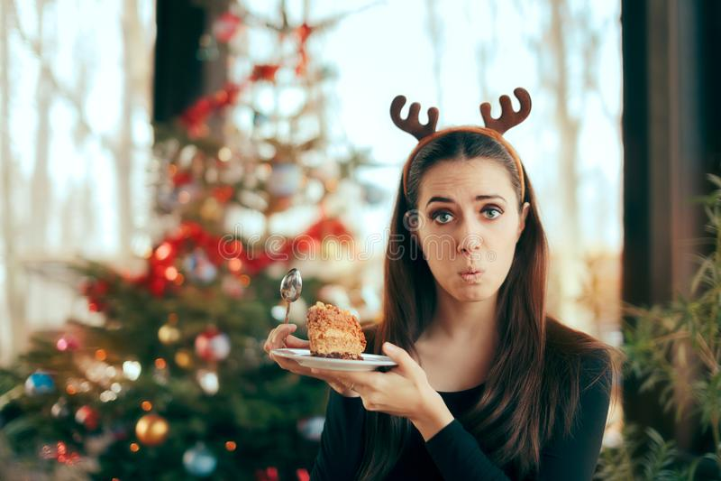 Muchacha criticona que odia la torta en el partido de cena de la Navidad foto de archivo
