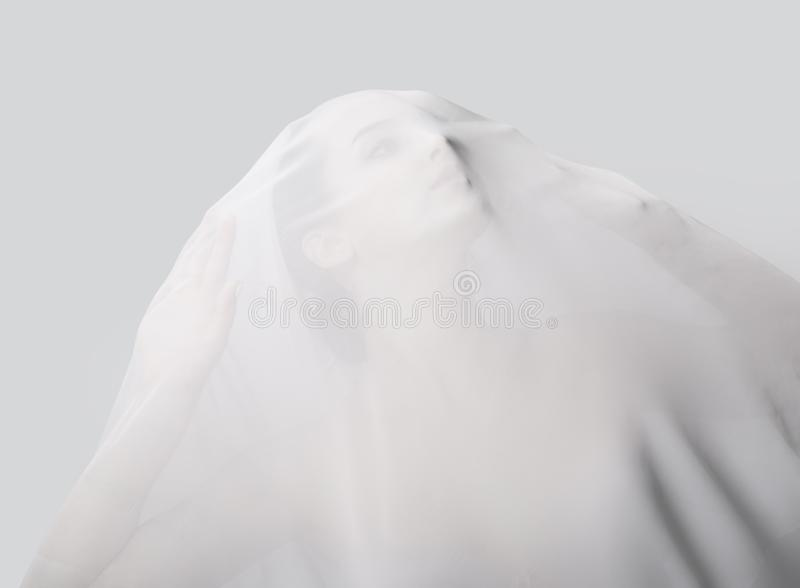 Muchacha cubierta con la tela translúcida blanca Ella mira para arriba fotos de archivo libres de regalías