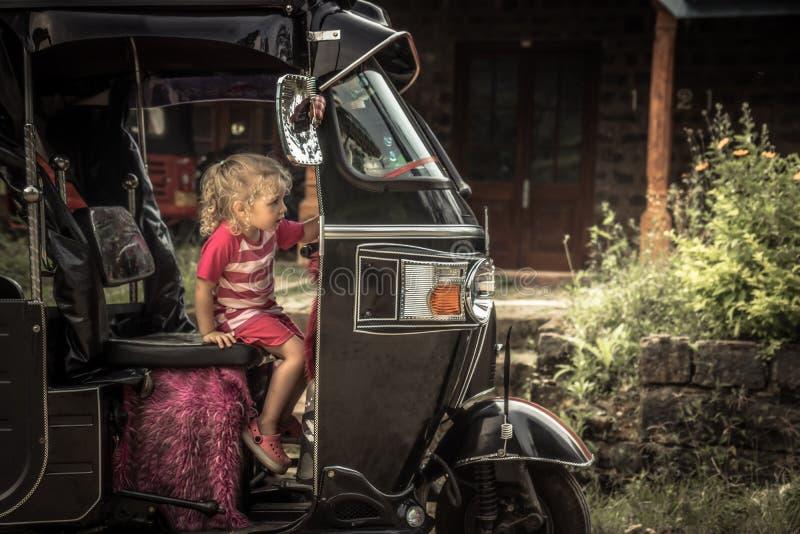 Muchacha curiosa del viajero del niño en el vehículo de motor del tuk del tuk durante forma de vida despreocupada feliz del viaje fotos de archivo