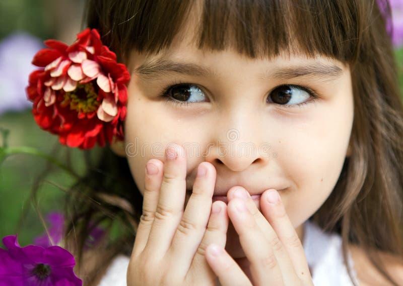 Muchacha curiosa hermosa con una flor foto de archivo libre de regalías