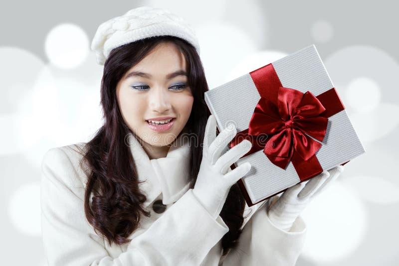 Muchacha curiosa que sostiene una caja de regalo fotos de archivo libres de regalías