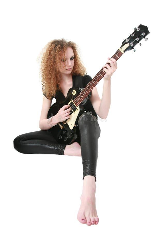 Muchacha Curly-haired que toca la guitarra imagen de archivo