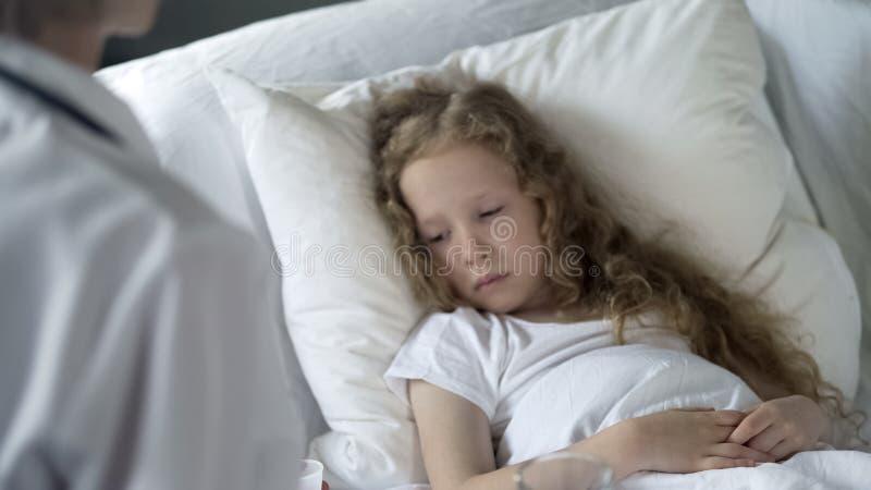 Muchacha d?bil enferma que miente en cama en hospital, paciente de examen del doctor, atenci?n sanitaria foto de archivo libre de regalías