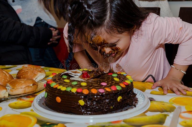 Muchacha de 6 años que celebra su cumpleaños poniendo su cara dentro de la torta fotografía de archivo libre de regalías