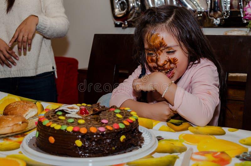 Muchacha de 6 años que celebra su cumpleaños poniendo su cara dentro de la torta fotos de archivo libres de regalías