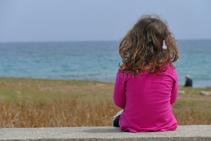 Muchacha de 3-4 años que mira el mar foto de archivo