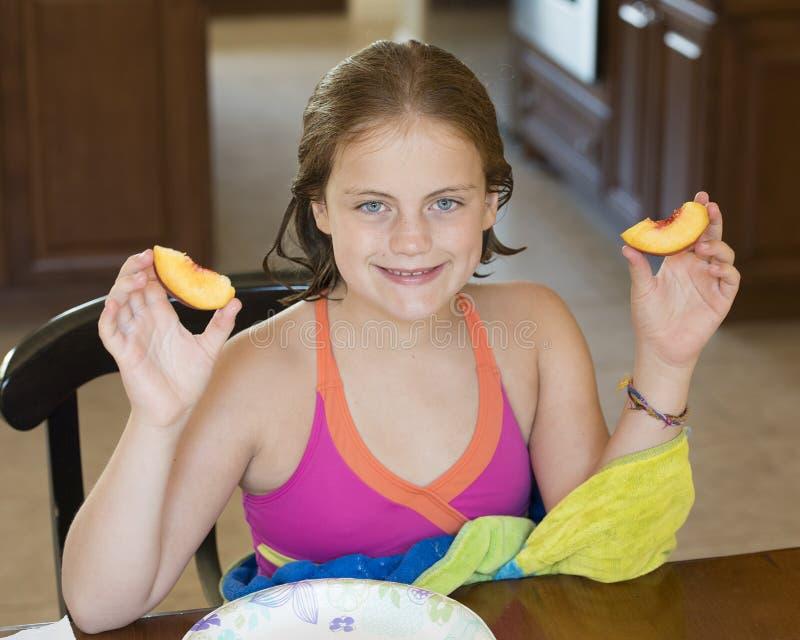 Muchacha de 10 años que se sienta en una tabla que lleva a cabo una rebanada del melocotón en cada mano foto de archivo libre de regalías