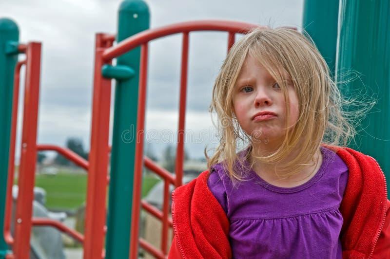 Muchacha de 4 años trastornada y que pone mala cara en el patio imagen de archivo libre de regalías