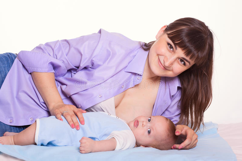 Muchacha de amamantamiento del bebé de la familia de la momia feliz linda de la madre en pizca imagen de archivo