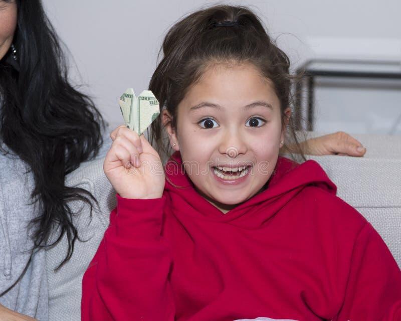 Muchacha de Amerasian entusiasta sobre su regalo de la Navidad, un billete de dólar veinte hecho en un corazón con oragami fotografía de archivo libre de regalías